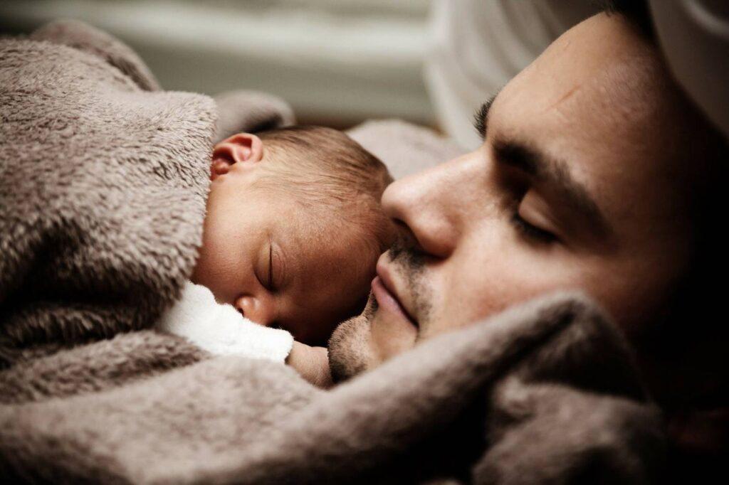 Padre e bambino che dormono nel letto