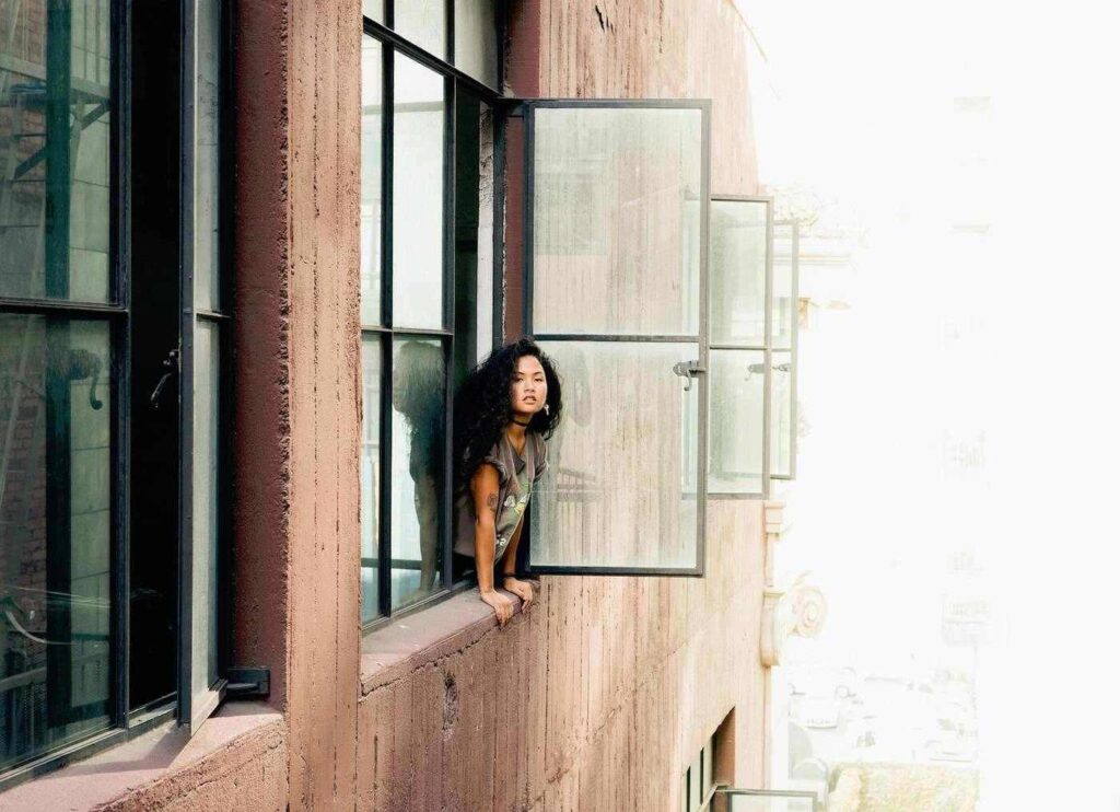 Woman leaning out of upstairs apartment window