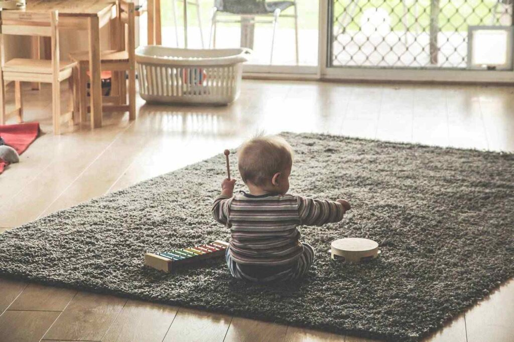 Baby playing xylophone and tambourine on carpet