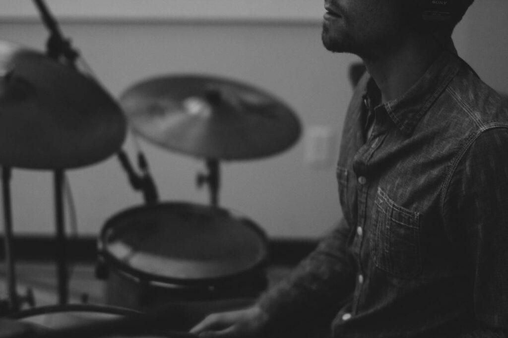 Uomo che suona musica con set di percussioni che include piatti