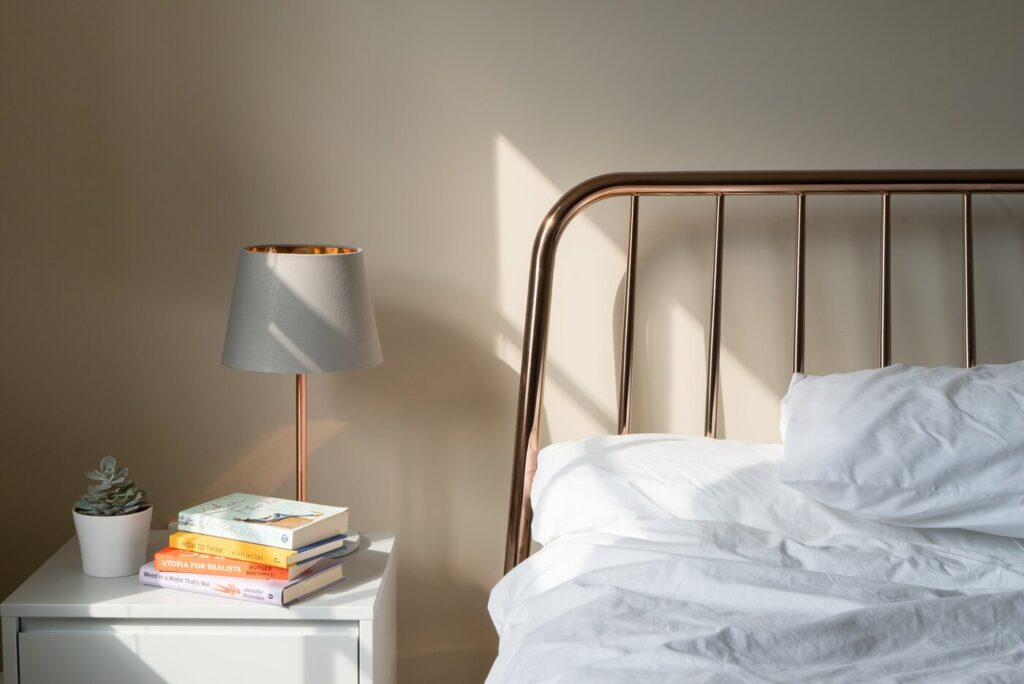 letto e comodino con libri e lampada - quello che devi sapere sull'insonorizzazione della tua camera da letto